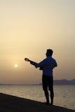 Gitarrist på soluppgång på stranden royaltyfria foton