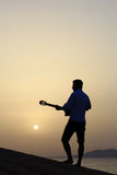 Gitarrist på soluppgång på stranden arkivfoton