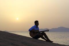 Gitarrist på soluppgång på stranden royaltyfri bild