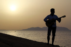 Gitarrist på soluppgång på stranden Royaltyfri Foto