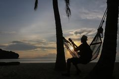 Gitarrist på stranden med soluppgången royaltyfria foton
