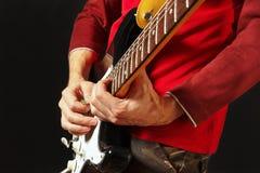 Gitarrist setzte Finger für Akkorde auf E-Gitarre auf schwarzem Hintergrund Stockfoto
