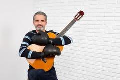 Gitarrist som bär, i att posera för boxninghandskar royaltyfri bild