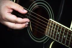 Gitarrist som klinkar den akustiska gitarren arkivfoton