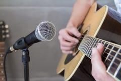 Gitarrist som klinkar en gitarr in i en mikrofon Royaltyfri Fotografi