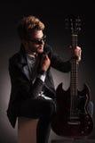 Gitarrist som rymmer hans elektriska gitarr och krage Royaltyfri Foto