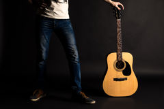 Gitarrist som rymmer hans vänstersidahand med en akustisk gitarr på en svart bakgrund royaltyfria foton