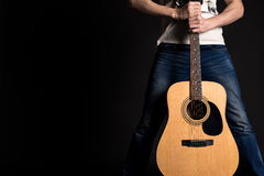 Gitarrist som rymmer två händer med en akustisk gitarr på en svart bakgrund royaltyfri bild