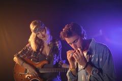 Gitarrist som ser musikern som spelar munspelet i musikkonsert royaltyfria bilder