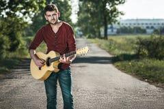 Gitarrist som sjunger på vägen arkivbild