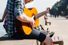 Gitarrist som spelar bredvid havet arkivfoto