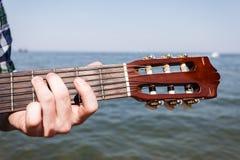 Gitarrist som spelar bredvid havet royaltyfria bilder