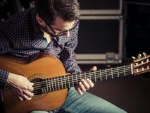 Gitarrist som spelar den akustiska gitarren i studio Arkivbild
