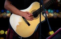 Gitarrist som spelar den akustiska gitarren med suddighetsljus Arkivbilder