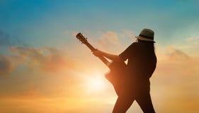 Gitarrist som spelar den akustiska gitarren på den färgrika cloudscapesolnedgången royaltyfria foton