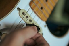 Gitarrist som spelar den elektriska gitarren med en hacka arkivbilder
