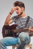Gitarrist som spelar det placerade instrumentet, medan tänka royaltyfria foton
