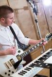 Gitarrist som spelar gitarren bredvid tangentborden arkivfoto
