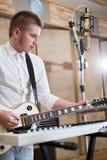 Gitarrist som spelar gitarren bredvid tangentborden arkivbilder