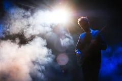 Gitarrist som spelar gitarren i mörker med blått tillbaka ljus royaltyfri bild