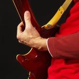 Gitarrist som spelar gitarren på mörk bakgrund royaltyfria bilder