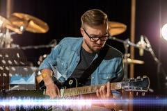 Gitarrist som spelar gitarren på studion för solid inspelning royaltyfri foto