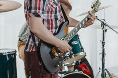 Gitarrist som spelar hans akustiska gitarr på en lokal konsert med hans musikband, och en annan gitarrist i bakgrunden fotografering för bildbyråer