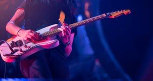 Gitarrist som spelar hans tappninggitarr på etapp Gitarr solo under royaltyfria bilder