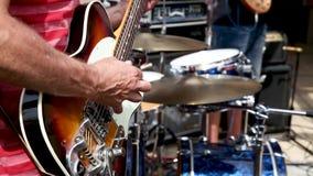 Gitarrist som spelar i en musikband på solig dag