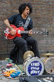Gitarrist som spelar i tegelstengränd arkivbilder