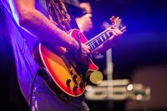 Gitarrist som spelar på den elektriska elbasen på etapp Färgrikt så royaltyfri fotografi