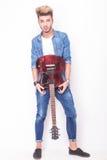 Gitarrist som visar hans röda elektriska gitarr Royaltyfri Foto