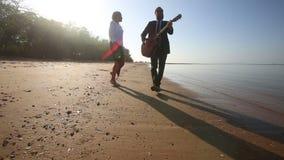 Gitarrist spielt und blondes Mädchen tanzt das Gehen entlang Strand stock footage