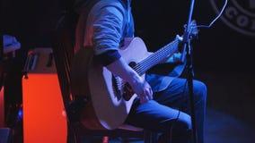 Gitarrist - ung man - akustisk gitarr för lekkonsert i nattklubb arkivfoto