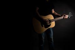Gitarristen i jeans spelar en akustisk gitarr, på rätsidan av ramen, på en svart bakgrund Horisontal inrama Royaltyfria Bilder