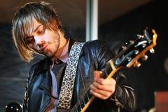 Gitarristen i läder klår upp med electroguitar fotografering för bildbyråer