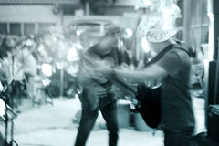 Gitarristen på gatan går på natten, tonar blått och begreppet för rörelsesuddighet Arkivbild