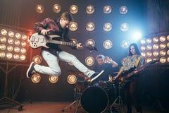 Gitarristen spelar på bas-gitarren, kort i ett hopp Royaltyfri Bild