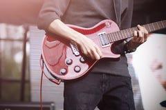 Gitarristen spelar p? en r?d elektrisk gitarr p? etapp under en konsert arkivbild