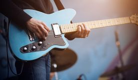 Gitarristen utför en melodi på en blå elektrisk gitarr fotografering för bildbyråer