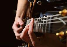 Gitarristhände, die Gitarre über Schwarzem spielen Stockfotos