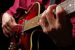 Gitarristhänder och nära övre för gitarr elektriskt leka för gitarr Leka gitarren arkivbilder
