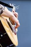 Gitarristhänder som spelar closeupen för akustisk gitarr arkivfoton