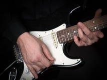 Gitarristhänder som spelar på den elektriska gitarren, slut upp, utvald fokus arkivfoto