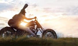 Gitarristkvinna som rider en motorcykel på bygdvägen Arkivfoton