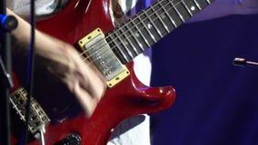 Gitarristrockband spielt Gitarre auf Stadium im Scheinwerfer stock video