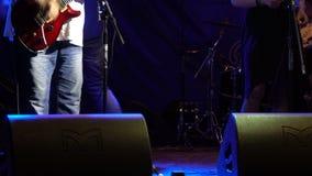Gitarristrockband spielt Gitarre auf Stadium im Scheinwerfer stock footage