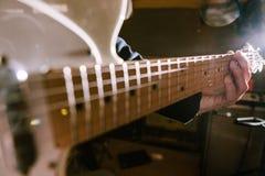 Gitarrriff i gitarristhänder i selektiv fokus arkivbild