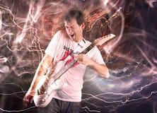 Gitarrspelare med den vita elektriska gitarren Arkivfoto