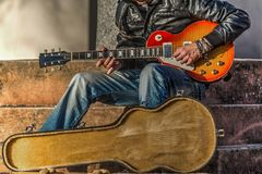 Gitarrspelare med ett öppet gitarrfall Arkivbild